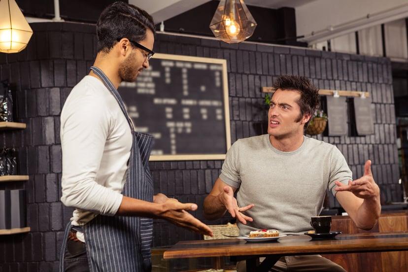An upset  restaurant customer complains to his waiter.jpg